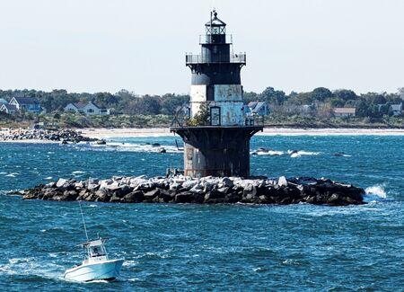 Una barca sta passando il faro di Orient Point in una giornata ventosa con mare mosso e la spiaggia sullo sfondo.