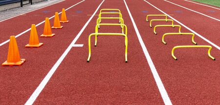 Cones and mini hurdles set up in lanes on a track for speed and agility practice.