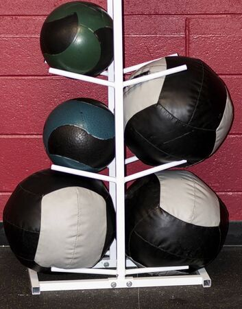 Different sizes of medicine balls on a white rack against a red wall inside a gym.