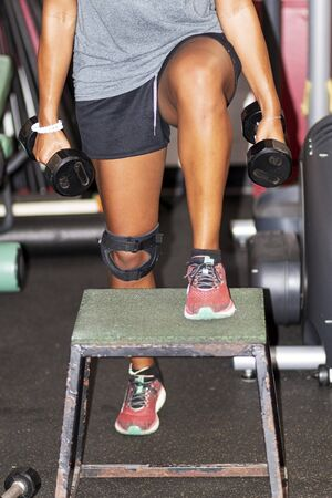 An African American girl is stepping up on a plyo box while holding dumbells in her hands inside a gym. Zdjęcie Seryjne