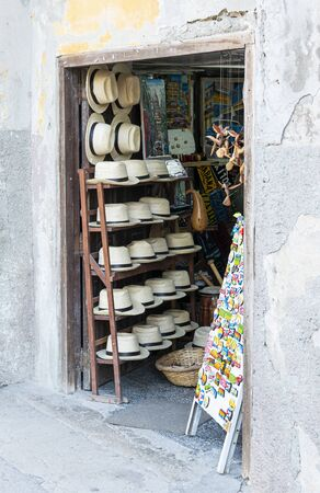 A small opening in a wall is a souvenir store selling homemade hats and Cuban items in Havana Cuba.
