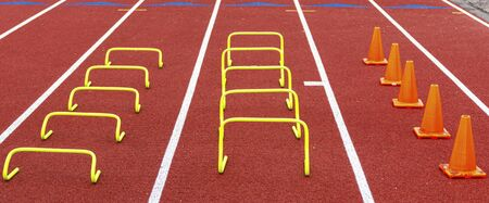 Yellow mini bannana hurdles and orange cones set up in lanes on a red track for speed and agility practice drills.