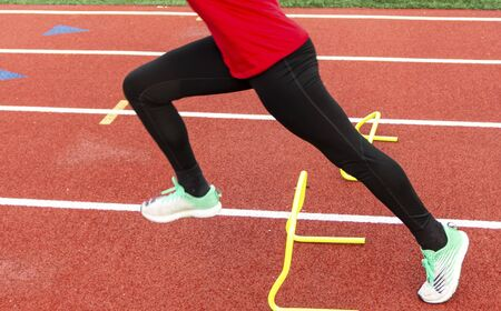 The legs of a high school runner performing a sprinters running drill over yellow mini hurdles on a red track.