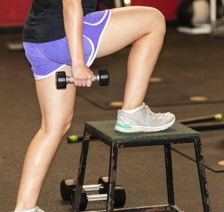 Side view inside a gym of a girl stepping up onto a plyo box while holding small dumbells in her hand.