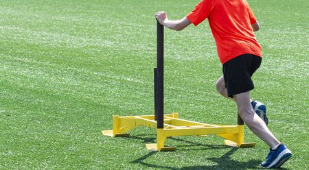 A teenage boy at a running camp is pushind a yellow weight sled on a green turf field. Zdjęcie Seryjne