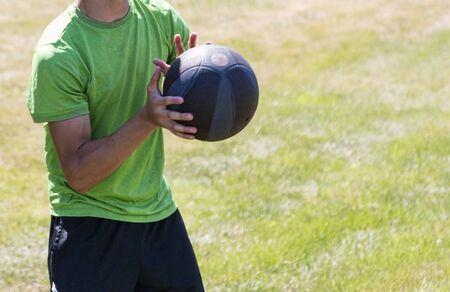 A young athlete is catching a medicine ball during strenght training on a green grass field during summer camp.
