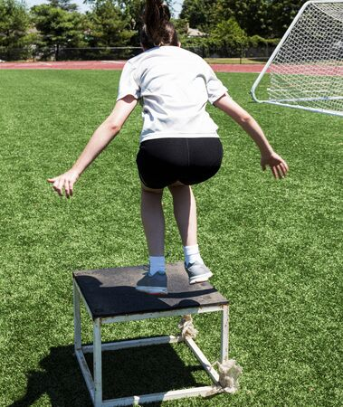 A young girl is jumping on to a plyo box on a green turf field during speed and agility summerr camp. Zdjęcie Seryjne