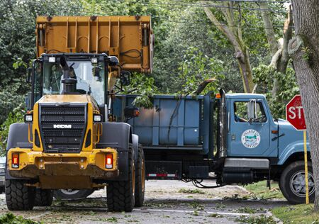 Babylon, New York, USA - 23 August 2019: Babylon Village trucks clearing a road full of trees after a hurricane and strong winds caused damge and trees to fall.
