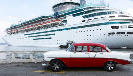 Havana, Cuba - 25 July 2018: A red and white classic restored Chevrolet Belair parked on the road in fron of a cruise ship in Havan Cuba.