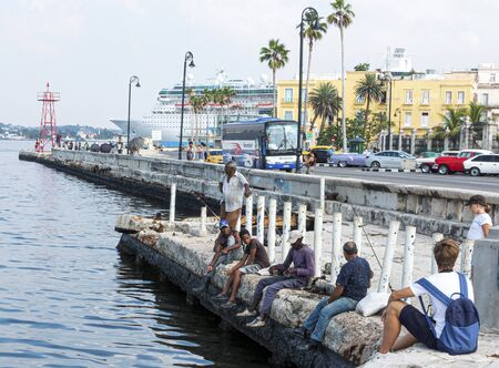 Havana, Cuba - 25 July 2018: People fishing in Havana Cuba next to Malecon road with a view of a cruise ship in the background.