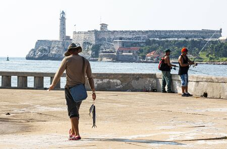 Havana, Cuba - 25 July 2018: Fisherman in Havana Cuba walking on the malecan with the fish he just caught and el morro castle in the background.