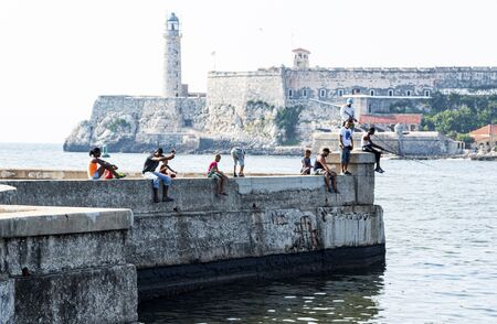 Havana, Cuba - 25 July 2018: People fishing while sitting on a cement wall located on the Malecon with El Morro Castle in the background in Havana Cuba. Publikacyjne