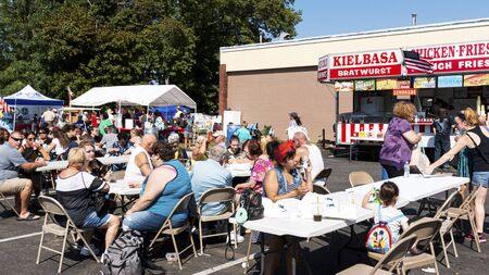 West Islip, New York, USA - 22 September 2019: People enjoying snacks sitting at tables in a parking lot during the annual community fair.