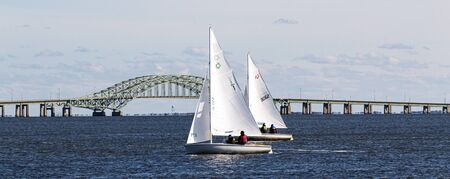 7 December 2019: Two small sailboats racing each other in a winter regatta in front of the Great South Bay bridge on the south shore of Long Island. Publikacyjne
