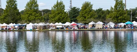Babylon, New York, USA - 8 September 2019: View across Argyle Lake of vendors tents and people walking during the annual Babylon Beautification Society Fair.