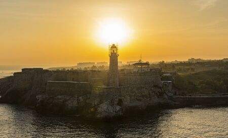 The sun rising just above the lighthouse lodated in El Morro castle Cuba.