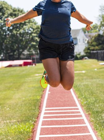 A high school female track and field athlete is practicng the long jump ad flying in the air at the camera. Zdjęcie Seryjne