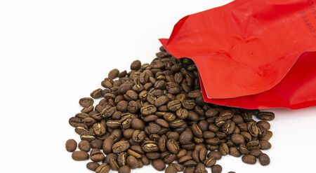 A red bag of fresh coffee beans is poured out on to a white background.