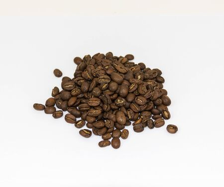A pile of fresh brown coffee beans with a white background. Zdjęcie Seryjne