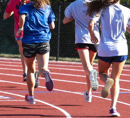 Rear view of a group of high school track girls running together on a red track while running intervals. Zdjęcie Seryjne