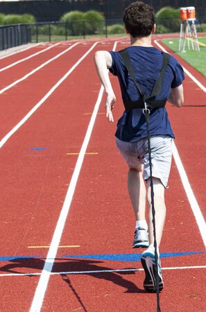 Rear view of a high school boy running while pulling a wieghted sled on a red track at summer camp.