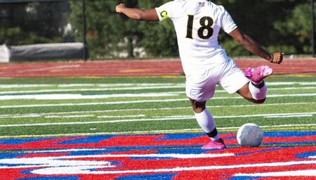 A high school boy soccer player is winding up to kick the ball with pink cleats.