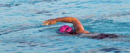 Horizontal view of a female swimmer swimming with a freestyle stroke in an outdoor pool training for a triathlon. Zdjęcie Seryjne