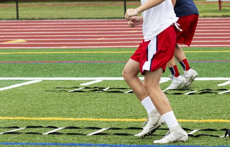 Two high school boys are running ladder drills on the turf during football summer camp. Zdjęcie Seryjne
