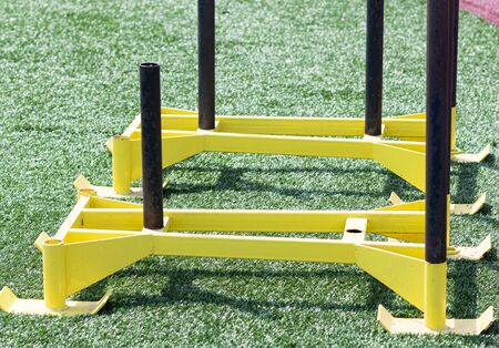 Close up of two yellow sleds used to put weight on an give athletes resistance while pushing to build strength. Archivio Fotografico