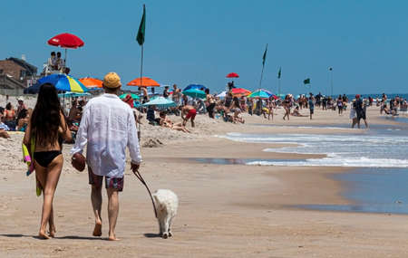 Ocean Beach, New York, USA - 27 May 2019: People enjoying a day on the beach at Ocean Beach on Fire Island, walking their dog, playing in the water and relaxing on the sand.