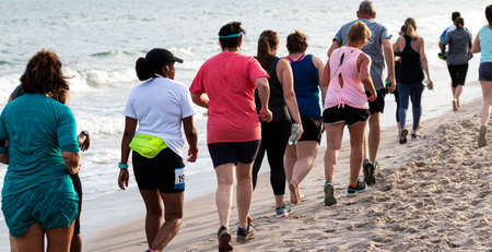 Babylon, New York, USA - 24 June 2019: Hundreds of people running and walking a one mile race on the beach next to the ocean waters, as part of the New York State Parks Summer Series of races.