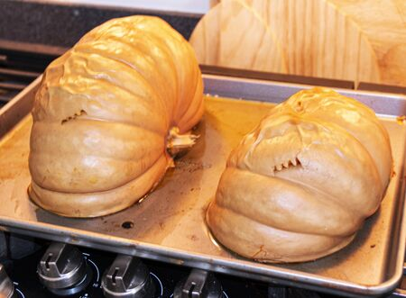 Two halfs of a freshly baked pumpkin just out of the oven preparing to make fresh pumpkin pie and bread.