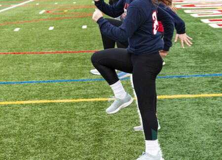 High school girls track and field team perfoming the speed drill A-Skip in a straight line on a green turf field.
