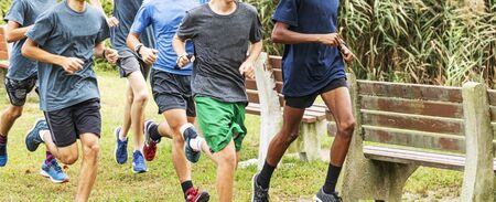 A group of high school boys are running together during cross country practice in a park passing benches.