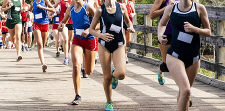 Girls running in a high school cross country race at Sunken Meadow State Park crossing a wood bridge during a 5K race.