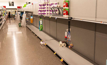 West Islip, New York, USA - 16 March 2020: A grocery store shelves are almost empty due to people hording toilet paper and paper towels during the corona virus pandemic. Редакционное