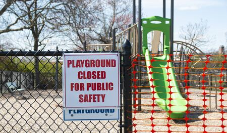 Playground closed for public safety sign posted on the fence of a play area in Babylon Village New York.