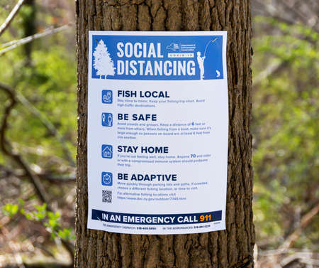 Babylon, New York, USA - 1 April 2020: A paper sign is staples to a tree in a park telling people to Social Distance, fish local, be safe, stay home and be adaptive. Sajtókép