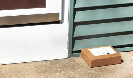 One small cardboard package is deleverd and left out in view on resedental front stoop. Stockfoto