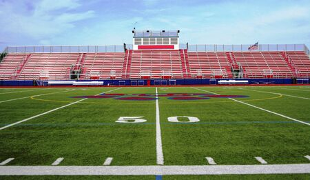 高中红色和白色露色的中间场视图有绿色人为草皮的在与蓝天的50个围场设置的。