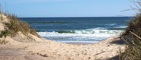 Looking through the dunes at the Atlantic Ocean on a sand footpath in Montauk New York Long Island USA. Stok Fotoğraf