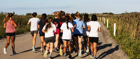 Rear view of a high school cross country coach and her athletes running together on a dirt road Фото со стока