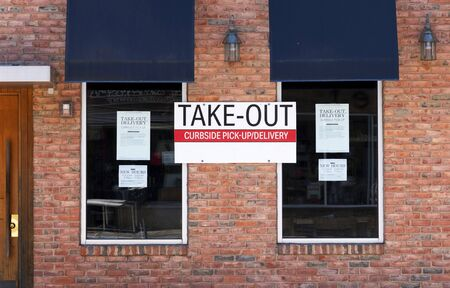 Take out curbside pick up or delivery only sign posted on the brick wall of a restaurant Фото со стока