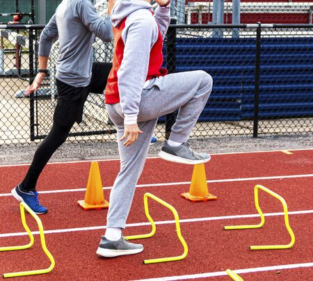 Two high school boys stepping over yellow mini hurdles and orange cones on a red track during track and field practice.