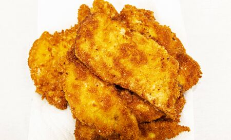 Many fried chicken pieces on top on one another with a white background looking from above. Фото со стока