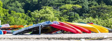 Horizontal view of many colorful kayaks stored on West Neck Beach with trees in the background.