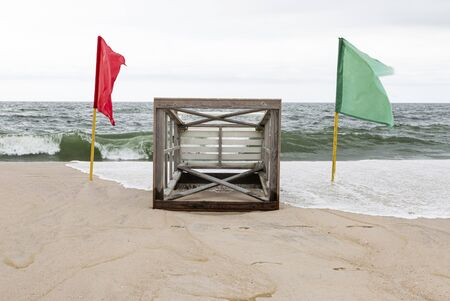 A lifeguard stand lying on the sand ot the beach with the ocean waves in background and red and green flag on either side as water rolls over.