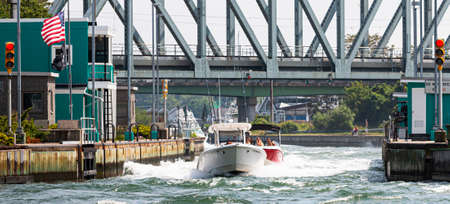 Hampton Bays, New York, USA - 6 June 2020: Boats moving through the rough waters in the Shinnecock Canal with the locks open. Редакционное