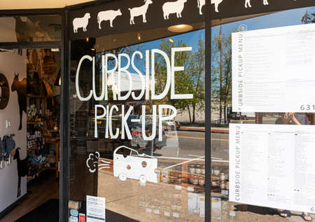Babylon, New York, USA - 13 May 2020: Due ot the coronavirus breakout a cheese store in Babylon Village is offering curbside pick up written on their front window.