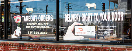 Babylon, New York, USA - 13 May 2020: Delivery by door dash available for takeout orders on the windows of a restaurant in Babylon Village due to the coronavirus COVID-19 outbreak.
